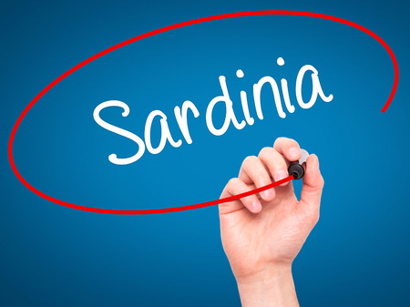 Man Hand writing Sardinia  with black marker on visual screen. Isolated on blue. Business, technology, internet concept. Stock Photo