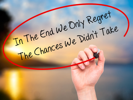 Man Hand writing In The End We Only Regret The Chances We Didn't Take with black marker on visual screen. Isolated on nature. Business, technology, internet concept. Stock Photo