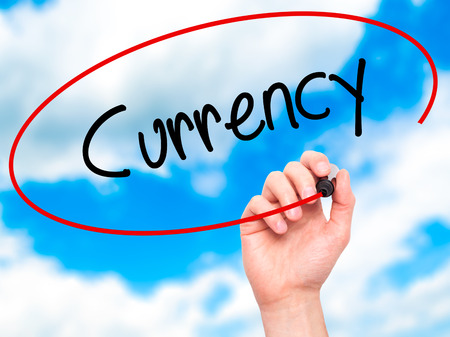 Man Hand writing Currency with black marker on visual screen. Isolated on sky. Business, technology, internet concept. Stock Photo