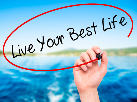 Man Hand writing Live Your Best Life with black marker on visual screen. Isolated on nature. Business, technology, internet concept. Stock Photo