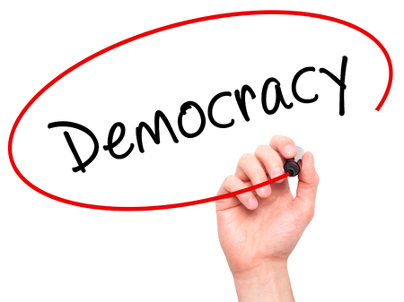 Man Hand writing Democracy with black marker on visual screen. Isolated on white. Business, technology, internet concept. Stock Image
