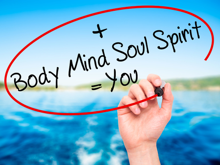 Man Hand writing Body + Mind + Soul + Spirit = You with black marker on visual screen. Isolated on nature. Life, technology, internet concept. Stock Image