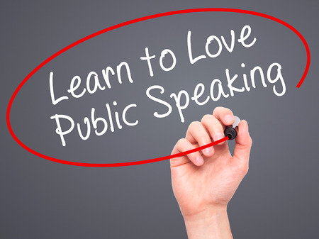 Man Hand writing Learn to Love Public Speaking with black marker on visual screen. Isolated on grey. Business, technology, internet concept. Stock Image