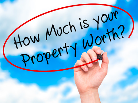 Foto für Man Hand writing How Much is your Property Worth? with black marker on visual screen. Isolated on sky. Business, technology, internet concept. Stock Image - Lizenzfreies Bild