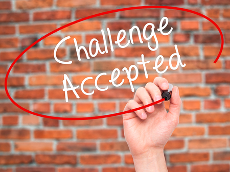 Man Hand writing  Challenge Accepted with black marker on visual screen. Isolated on bricks. Business, technology, internet concept. Stock Photo
