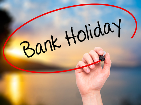 Foto de Man Hand writing Bank Holiday with black marker on visual screen. Isolated on background. Business, technology, internet concept. Stock Photo - Imagen libre de derechos