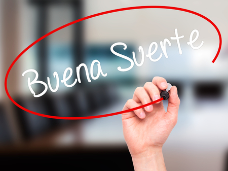 Man Hand writing Buena Suerte( Good Luck in Spanish) with black marker on visual screen. Isolated on office. Business, technology, internet concept. Stock Photo