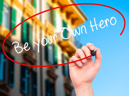 Man Hand writing  Be your Own Hero  with black marker on visual screen. Isolated on city. Business, technology, internet concept. Stock Photo