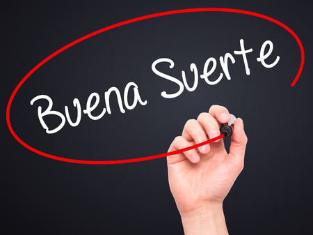 Man Hand writing Buena Suerte( Good Luck in Spanish) with black marker on visual screen. Isolated on black. Business, technology, internet concept. Stock Photo