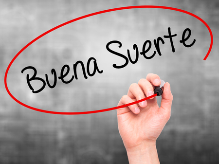 Man Hand writing Buena Suerte( Good Luck in Spanish) with black marker on visual screen. Isolated on grey. Business, technology, internet concept. Stock Photo