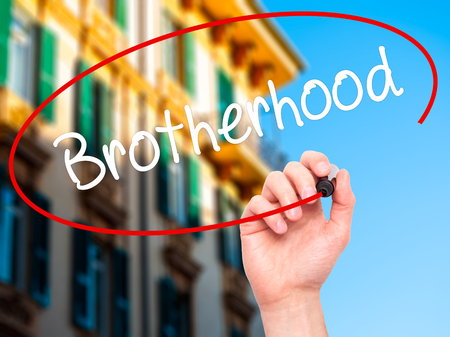 Man Hand writing  Brotherhood  with black marker on visual screen. Isolated on background. Business, technology, internet concept. Stock Photo