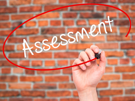 Man Hand writing Assessment with black marker on visual screen. Isolated on bricks. Business, technology, internet concept. Stock Photo