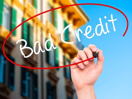 Man Hand writing Bad Credit with black marker on visual screen. Isolated on city. Business, technology, internet concept. Stock Photo