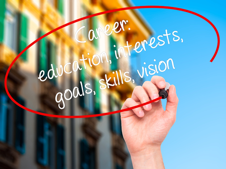 Man Hand writing Career: education, interests, goals, skills, vision with black marker on visual screen. Isolated on city. Business, technology, internet concept.