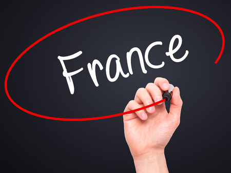 Man Hand writing France with black marker on visual screen. Isolated on black. Business, technology, internet concept. Stock Photo