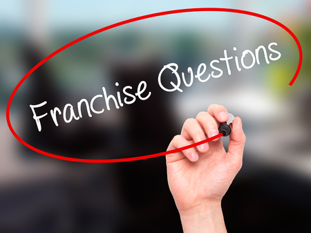 Man Hand writing Franchise Questions with black marker on visual screen. Isolated on office. Business, technology, internet concept. Stock Photo