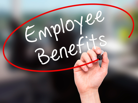 Man Hand writing Employee Benefits with black marker on visual screen. Isolated on office. Business, technology, internet concept. Stock Photo