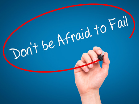 Man Hand writing Don't be Afraid to Fail with black marker on visual screen. Isolated on blue. Business, technology, internet concept. Stock Photo