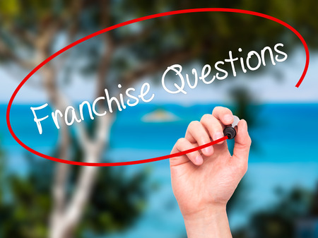 Man Hand writing Franchise Questions with black marker on visual screen. Isolated on nature. Business, technology, internet concept. Stock Photo