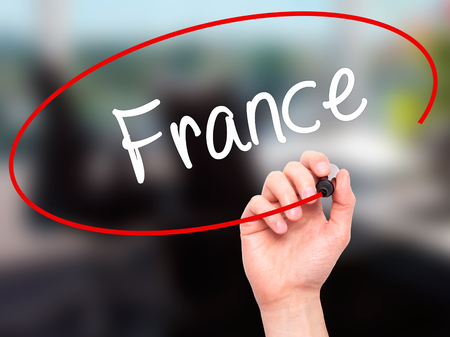 Man Hand writing France with black marker on visual screen. Isolated on office. Business, technology, internet concept. Stock Photo