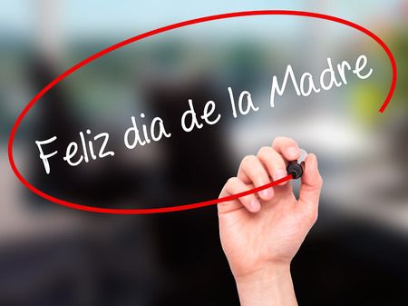 Man Hand writing Feliz dia de la Madre (Happy Mothers Day in Spanish)  with black marker on visual screen. Isolated on office. Business, technology, internet concept. Stock Photo