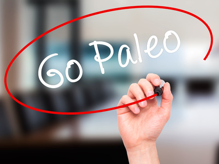 Man Hand writing Go Paleo with black marker on visual screen. Isolated on office. Business, technology, internet concept. Stock Photo