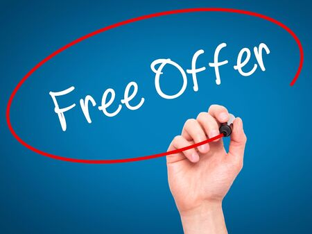 Man Hand writing Free Offer  with black marker on visual screen. Isolated on blue. Business, technology, internet concept. Stock Photo