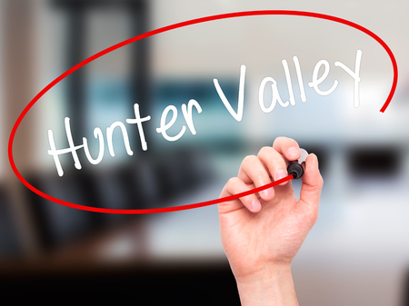Man Hand writing Hunter Valley  with black marker on visual screen. Isolated on office. Business, technology, internet concept. Stock Photo