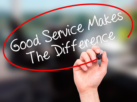 Photo pour Man Hand writing Good Service Makes The Difference with black marker on visual screen. Isolated on office. Business, technology, internet concept. Stock Photo - image libre de droit