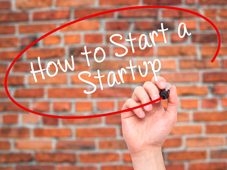 Man Hand writing How to Start a Startup with black marker on visual screen. Isolated on background. Business, technology, internet concept. Stock Photo