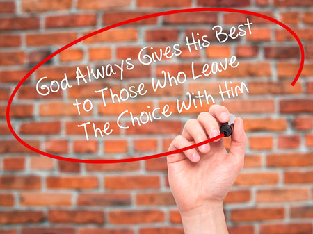 Man Hand writing God Always Gives His Best to Those Who Leave The Choice With Him with black marker on visual screen. Isolated on bricks. Business, technology, internet concept. Stock Photo