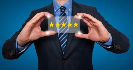 Photo pour Businessman holding five star rating. Blue - Stock Image - image libre de droit