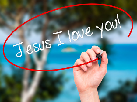 Man Hand writing Jesus I love you! with black marker on visual screen. Isolated on nature. Business, technology, internet concept. Stock Photo