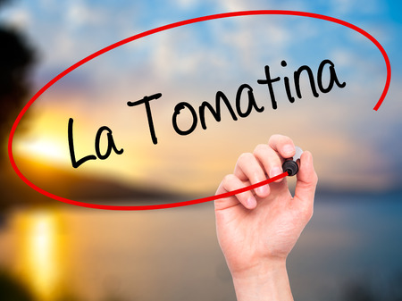 Man Hand writing La Tomatina with black marker on visual screen. Isolated on nature. Business, technology, internet concept.