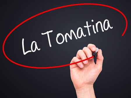 Man Hand writing La Tomatina with black marker on visual screen. Isolated on black. Business, technology, internet concept.