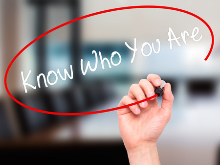 Man Hand writing Know Who You Are with black marker on visual screen. Isolated on office. Business, technology, internet concept.