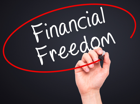 Man Hand writing Financial Freedom with black marker on visual screen. Isolated on black. Business, technology, internet concept. Stock Photo