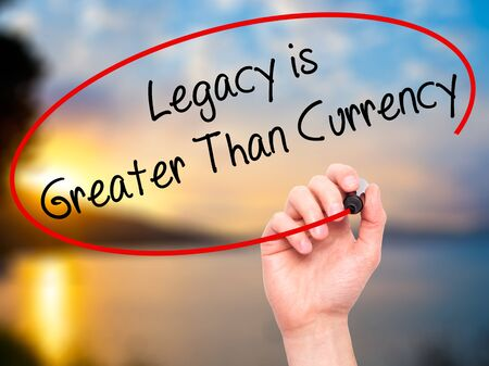 Photo pour Man Hand writing Legacy is Greater Than Currency with black marker on visual screen. Isolated on background. Business, technology, internet concept. Stock Photo - image libre de droit