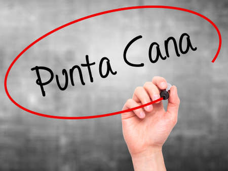 Man Hand writing Punta Cana with black marker on visual screen. Isolated on grey. Business, technology, internet concept. Stock Photo
