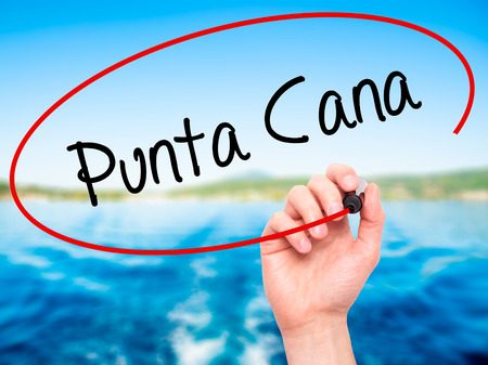 Man Hand writing Punta Cana with black marker on visual screen. Isolated on nature. Business, technology, internet concept. Stock Photo