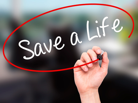 Man Hand writing Save a Life  with black marker on visual screen. Isolated on office. Business, technology, internet concept. Stock Photo