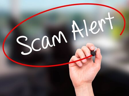 Man Hand writing Scam Alert  with black marker on visual screen. Isolated on office. Business, technology, internet concept. Stock Photo