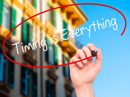 Man Hand writing Timing is Everything with black marker on visual screen. Isolated on city. Business, technology, internet concept. Stock Photo