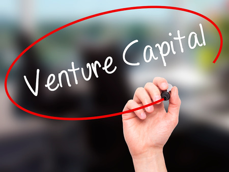 Man Hand writing Venture Capital with black marker on visual screen. Isolated on office. Business, technology, internet concept. Stock Photo