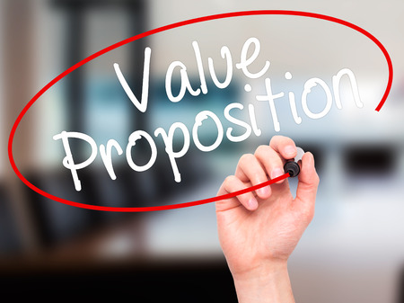 Man Hand writing Value Proposition with black marker on visual screen. Isolated on office. Business, technology, internet concept. Stock Photo