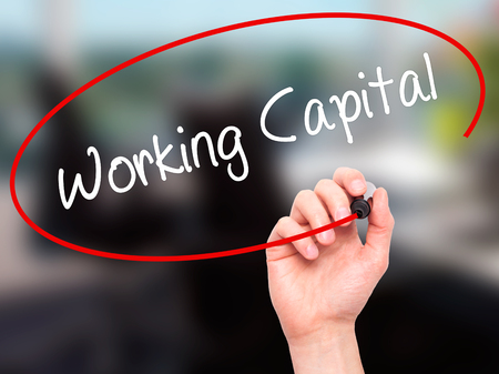 Man Hand writing Working Capital with black marker on visual screen. Isolated on office. Business, technology, internet concept. Stock Photo