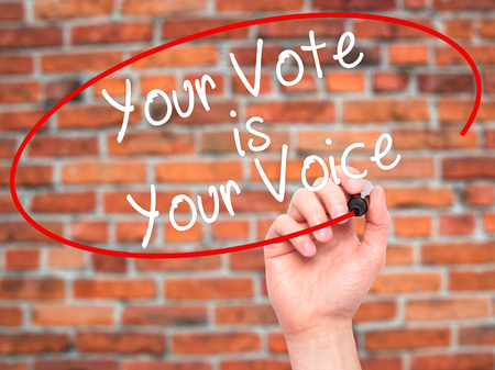 Man Hand writing Your Vote is Your Voice with black marker on visual screen. Isolated on bricks. Business, technology, internet concept. Stock Photo