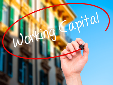 Man Hand writing Working Capital with black marker on visual screen. Isolated on city. Business, technology, internet concept. Stock Photo