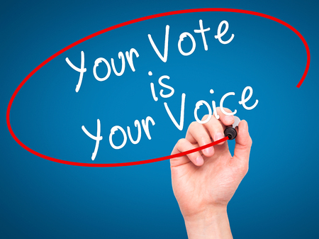 Man Hand writing Your Vote is Your Voice with black marker on visual screen. Isolated on blue. Business, technology, internet concept. Stock Photo