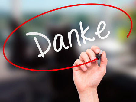 Man Hand writing Danke with marker on transparent wipe board. Isolated on office. Business, internet, technology concept. Stock Photo